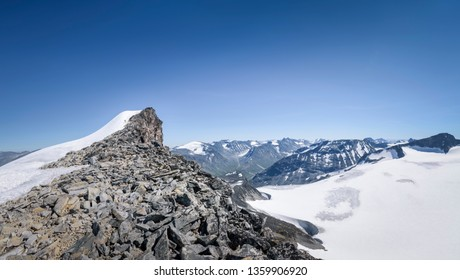Hiker near the top of mountain in big panorama of Jotunheimen National Park Noway