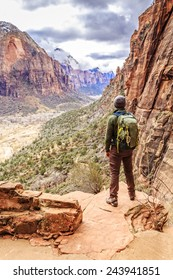 Hiker on Angels Landing Trail is a 5 mile trail that culminates on Zion National Park's iconic, dizzying ridge & offers stunning canyon views.