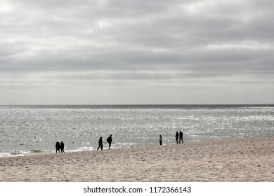 Hiker on the beach in backlight on the island of Sylt, Germany