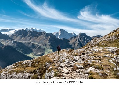 Hiker on dolomites path with Marmolada glacier in the background