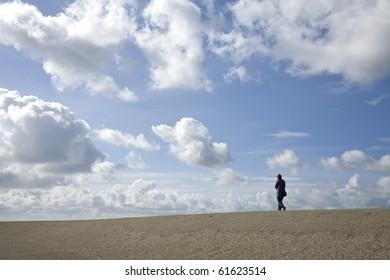 Hiker on a Dutch dike against a blue cloudy sky