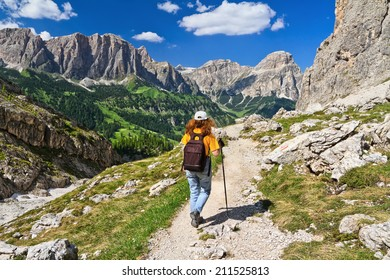 hiker on footpath  in Sella mountain, on background Colfosco and Badia Valley, south Tyrol, Italy