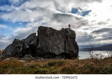 Hiker on a huge Stonee on the Kungsleden hiikintrail in Sweden