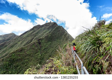Hiker on a lush a ridge trail on Oahu, Hawaii overlooking Kaneohe, Kailua and the windward side of the island