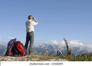 Hiker on mountain summit looking through field glasses
