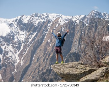 Hiker on mountain top standing arms outstretched celebrating achievement and feeling positive being on top of it all. People outdoor activities success concept