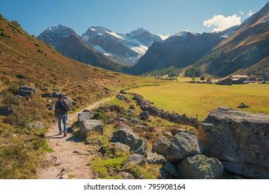 hiker on mountain trail at idyllic swiss valley near davos