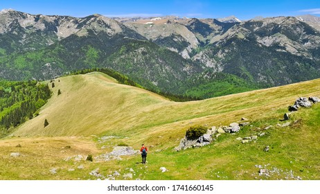 hiker on Oslea Mountain, Valcan Mountains, Romania, a beautiful spring day, viewpoint to Retezat Mountains.