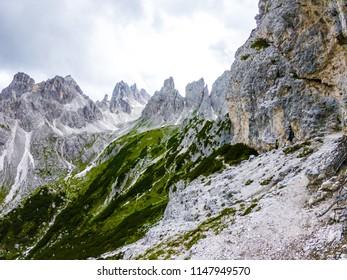 Hiker on the ridge of Dolomites Mountains in Alps, Italy. Via ferrata trail. Peole on the rocky mountains path. Travel in Dolomites. Adventure in the mountains. Mountain climber on an exposed ledge
