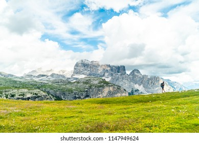 Hiker on the ridge of Dolomites Mountains in Alps, Italy. Via ferrata trail. Peole on the rocky mountains path. Travel in Dolomites. Adventure in the mountains. Mountain climber on an exposed ledge