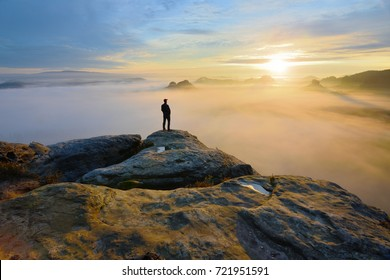 Hiker on rock end above valley. Man watch over misty and autumnal morning valley to bright morning Sun. Tourist  looking to misty valley bellow. Autumn cold weather