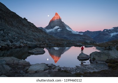 Hiker on a rock in the Riffelsee at sunrise, enjoying the Matterhorn view.