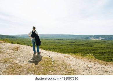 Hiker on a rocky outcrop enjoying a mountain view