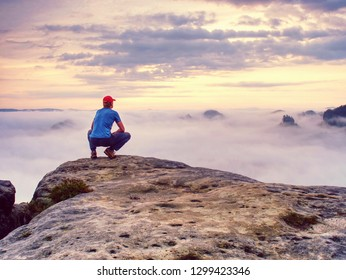 Hiker on sharp cliff of sandstone rock in rock empires park observe misty and foggy spring valley