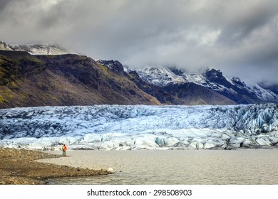 Hiker on the shore of Fjallsarlon lagoon at a glacier terminus in the south of Iceland