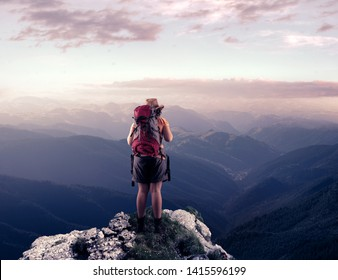 Hiker on top of a mountain peak admiring the view.