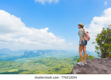 Hiker on the top of mountain. Tourist travel with backpack and hat in national park. Woman looking on valley with beautiful rocks.  Travel concept.