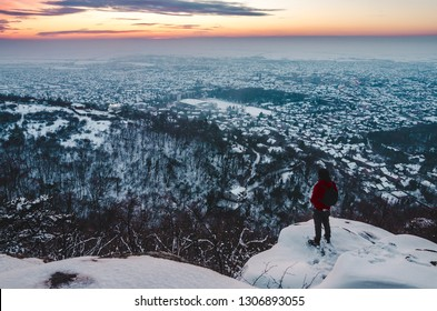 Hiker on a viewpoint above city under the colorful sky on a winter sunny day. Vrsac, Serbia.