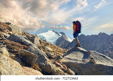 Hiker in orange shirt with big backpack looking on the snowy summit at background