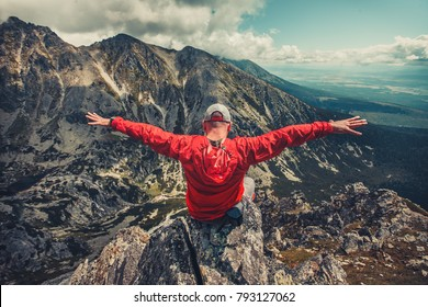 A hiker in outdoor red windbreaker jacket enjoys the magnificent view sitting on the edge of precipice in the Tatra Mountains in Slovakia. The feeling of strength and power. Wonderful panoramic view.
