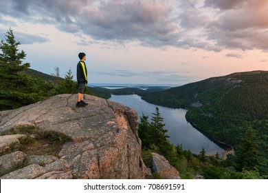 hiker overlooking Jordan Pond in Acadia National Park at sunset