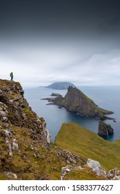 A hiker overlooks and an overcast, dramatic yet vibrant landscape scene over at Drangarnir and Tindholmer in the Faroe Islands.