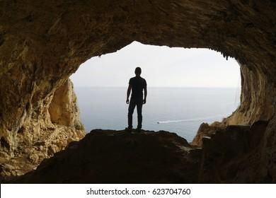 Hiker pauses to watch the sea from a cave, Grotta dei Falsari,  Noli, Liguria, Italy
