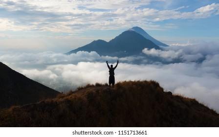hiker person rising hand standing on walk way at volcano Batur, Bali island, Indonesia