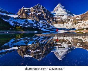 Hiker person walking along the Lake Magog with Mount Assiniboine in the background, British Columbia, Canada