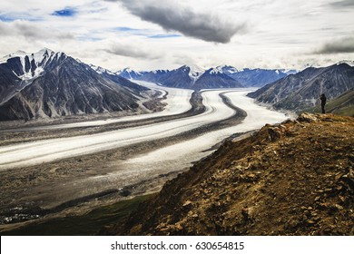 Hiker photographing beautiful Kaskawulsh Glacier in Kluane National Park, Yukon, Canada. Source of Slim river. Moraine, glacial retreat, global warming, river diversion, melting, St. Elias mountains.