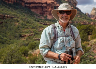 Hiker posing in desert scene cowboy hat adventure portrait strong smiling man Caucasian