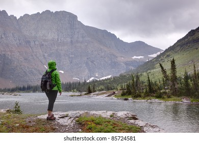 Hiker in Rainy Weather Looking at Mountains