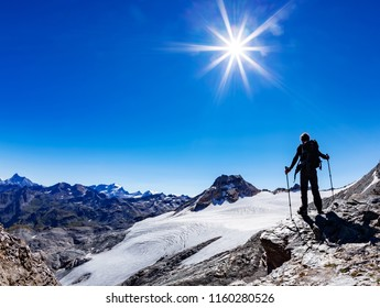 Hiker reaches a high mountain pass, Italian Alps, Val D'Aosta, Italy. Gran Paradiso National Park. Adult male caucasian model; sunny summer day. Concept: adventure, success, happiness, endurance.