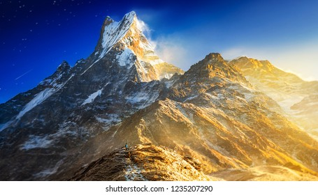Hiker reaches the mountain peak of Machapuchare. A mountain in the Annapurna Himalayas of north central Nepal. View point from Mardi Himal base camp track