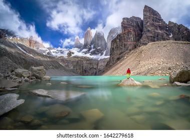 Hiker in red jacket admiring 3 peaks at Base de las Torres viewpoint in Torres del Paine, Patagonia