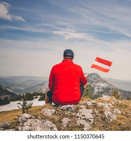 hiker with red sweater is holding an austria flag in the mountains