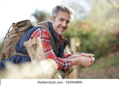 Hiker relaxing by fence on country track