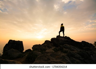 Hiker relaxing on top of a mountain and enjoying valley view during sunrise at Doi Pha Tang, Chiangrai, Thailand.