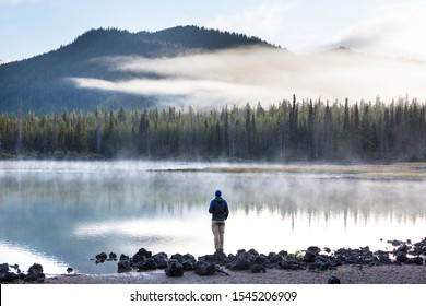 Hiker relaxing at serene mountain lake