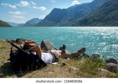 hiker resting on backpack near Gjende lake in Jotunheimen National Park, Norway