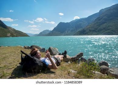hiker resting on backpack and taking photo of Gjende lake in Jotunheimen National Park, Norway