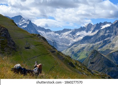 Hiker resting on green grass near ski station Les deux Alpes and view on Alpine mountains peaks in summer, Les Ecrins range, Isere, France - Shutterstock ID 1860277570