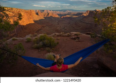 Hiker rests on a hammock admiring the sunset East Fork Shafer Canyon near Dead Horse Point State Park Canyonlands Utah