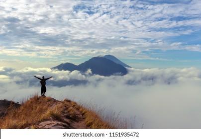 Hiker  rising hands on walk way at volcano Batur, Bali island, Indonesia