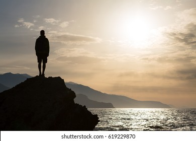 Hiker or runner silhouette backpacker, man looking at inspirational ocean landscape and islands on mountain peak. Accomplished man celebrate beautiful sunrise and sea. Adventure and lifestyle concept.