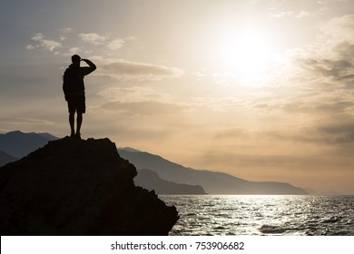 Hiker or runner silhouette backpacker, man looking at inspirational ocean landscape and islands on mountain peak. Accomplished man celebrate beautiful sunrise and sea.Adventure and lifestyle concept.