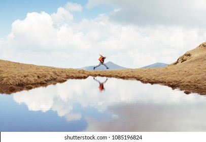 Hiker running on the mountain. Cheerfull man jumping. Hiking, sports, adventure, happiness, freedom