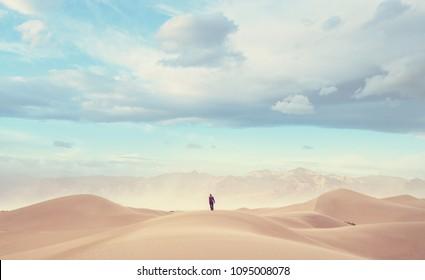 Hiker in sand desert. Sunrise time.