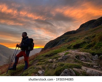 Hiker silhouette at sunset on the Langdale pikes in the Lake District