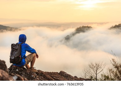 A hiker sit on the rock at view point to see sea fog in the morning
